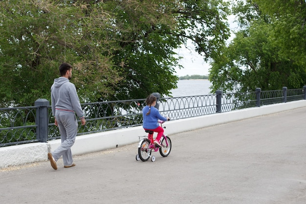 Dad teaches daughter to ride a pink bike on the river bank.