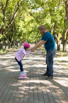 Dad teaches daughter to roller skate in the park