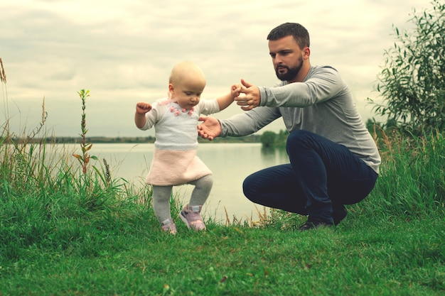 Dad teaches daughter to walk, park, nature. walk on the grass. father and daughter. first steps.