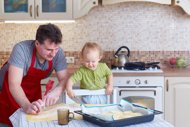 お父さんは小さな子供に一緒にクッキーやペストリーを焼く準備をするように教えます