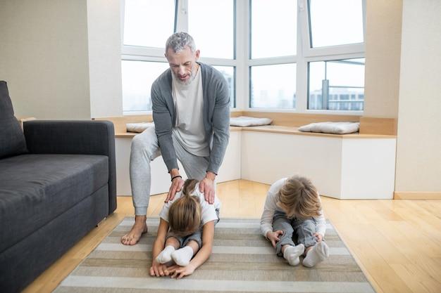 집에서 아이들에게 요가 운동을 가르치는 아빠