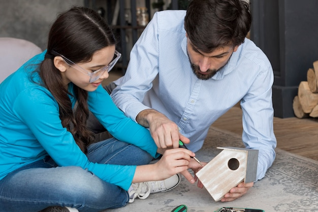 Dad teaching girl to build bird house