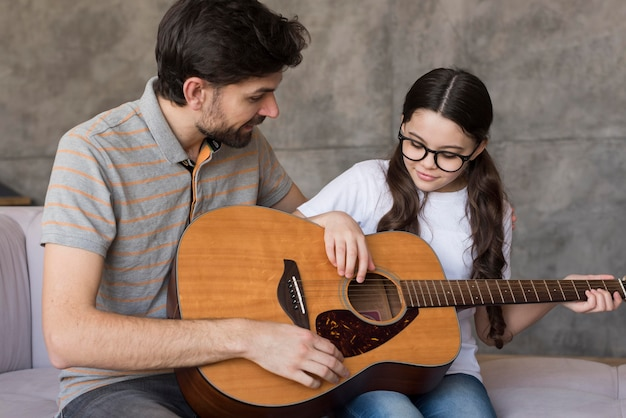 Dad teaching girl to play guitar