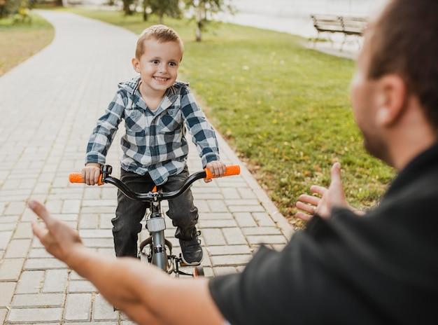 お父さんが子供に自転車の乗り方を教えている 無料写真