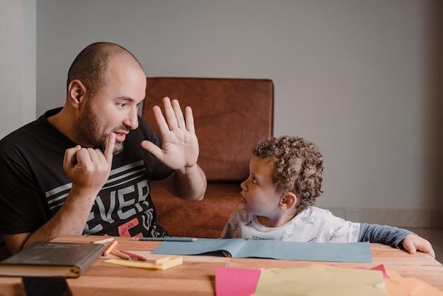 손가락으로 아들에게 숫자를 가르치는 아빠