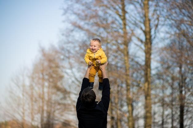 아빠가 노란색 재킷을 입은 아기를 공중에 던지고, 아이는 웃고 즐거워합니다.
