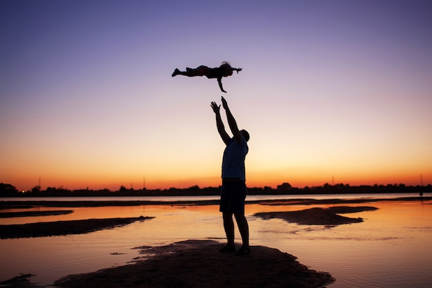 Dad throws the baby high silhouette photo