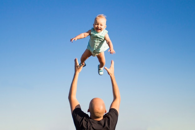 Dad throws his child up against the blue sky.