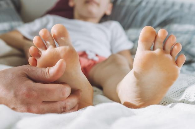 Папа щекочет ножки малыша. мальчик лежит на кровати и играет со своим отцом. семья, весело проводящая время дома