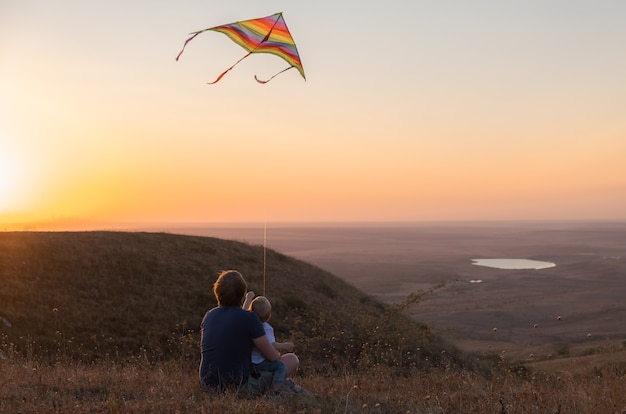 Dad and toddler boy son fly a kite at sunset.