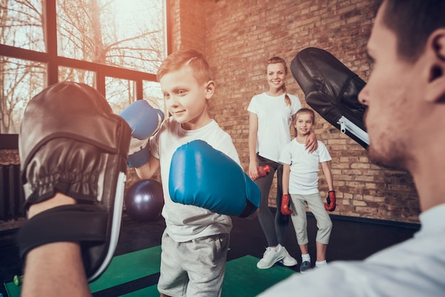 Dad trains little boxer in gloves in gym.