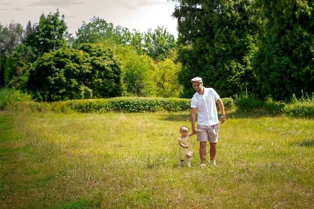 아빠는 초원 여름 시간에 그의 작은 아기 딸과 함께 산책