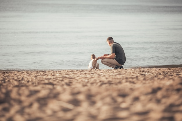 Dad walks with his son on the beach.