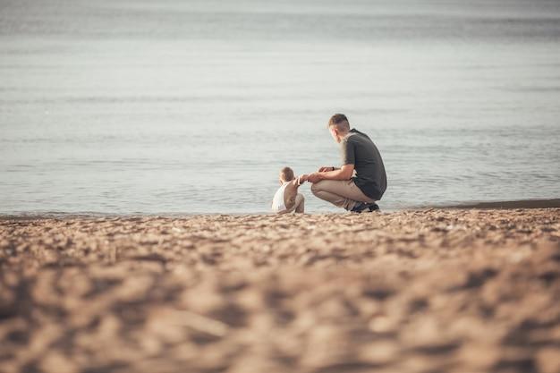 Папа гуляет с сыном по пляжу.