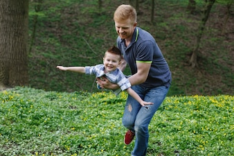 Dad whirls his son like an airplane playing in the green park