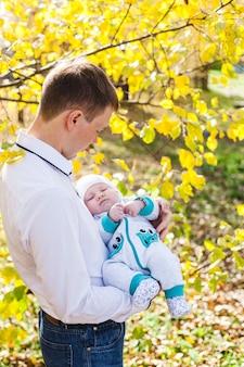 아기와 아빠, 작은 소년이 공원이나 숲에서 가을을 걷습니다. 노란 잎, 자연의 아름다움. 자녀와 부모 간의 의사 소통.