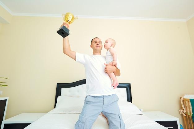 아이와 함께 컵 chempionship 슈퍼 아빠를 들고 아기와 아빠 부모와 어린 시절의 개념