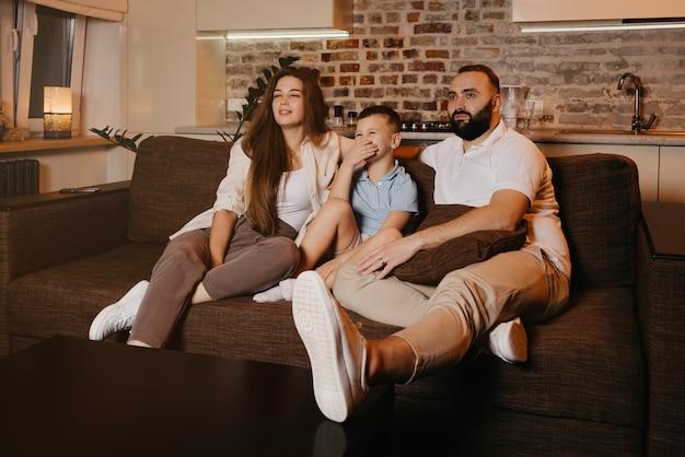 Папа с бородой, сын и молодая мама с длинными волосами смотрят телевизор и улыбаются на диване