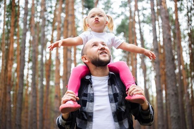 森でのハイキング中に子供とお父さん。山や森への家族のハイキング。
