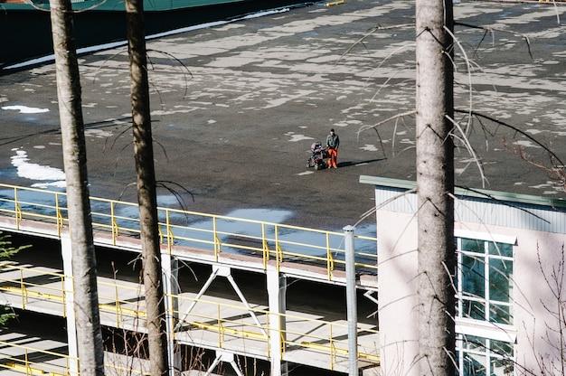 유모차에 아기를 안고있는 아빠는 고층 빌딩의 지붕에 올라와 걷습니다. 자동차 주차.