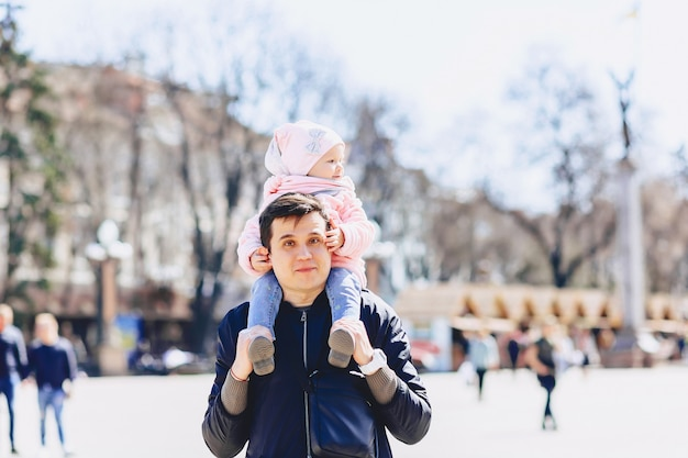 Dad with baby at shoulders walk on street