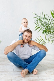 Dad with baby son around his neck having fun on a white background, happy fatherhood and family
