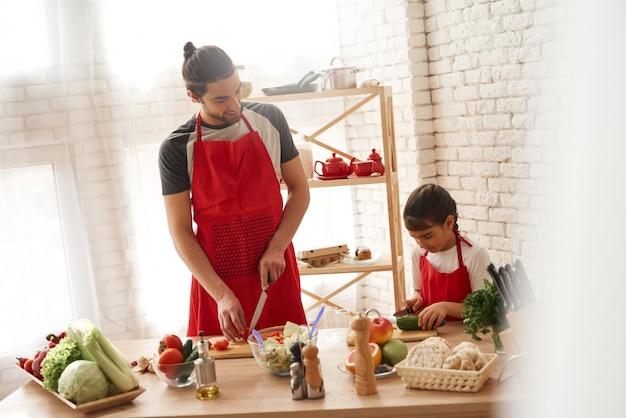Dad with daughter cutting veggies on kitchen.