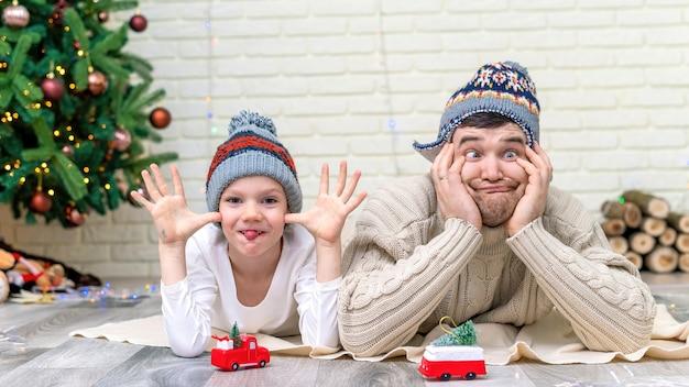 그의 아들과 아빠는 집에서 크리스마스 트리 근처 바닥에서 놀고 있습니다. 행복한 가족 아이디어