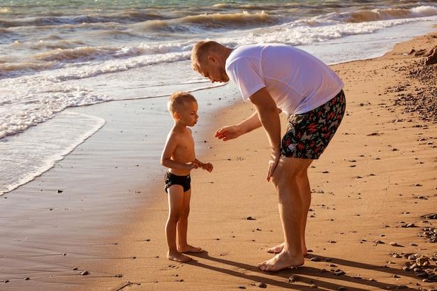 晴れた日の休暇で幸せな子供とビーチで彼の息子と若い白人の父のお父さん