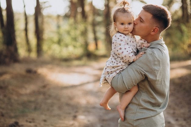 Dad with little daughter hugging in forest