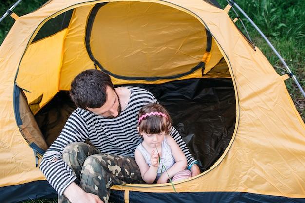 キャンプでテントの中で小さな娘とお父さん