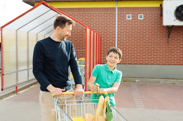 Dad with son went shopping together and walk to car with shopping cart, spend time together