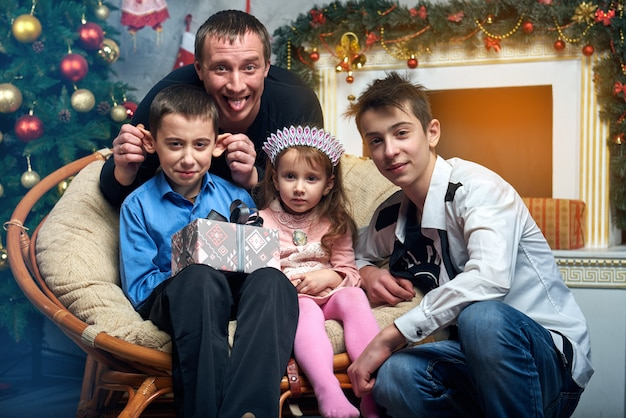 Dad with three children near the tree by the fireplace with gifts.