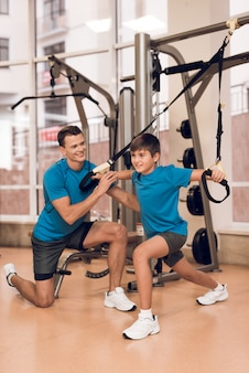 Dad and young son do exercise in the gym.