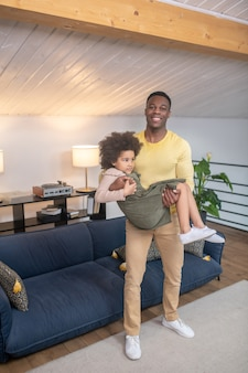 Dad. young strong dark skinned smiling dad in casual clothes standing holding curly little daughter in arms at home