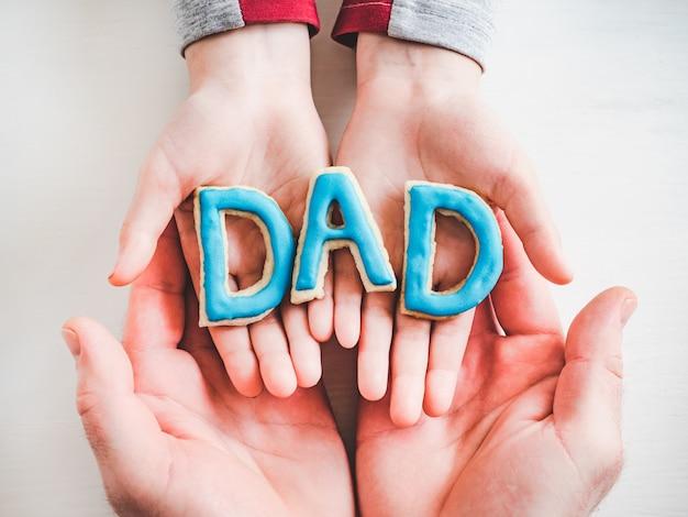 艶をかけられたクッキーから成っている単語dad。閉じる