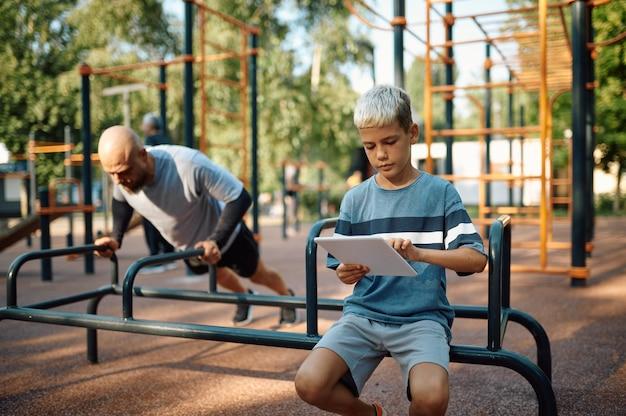 エクササイズマシンのパパと男の子、屋外の遊び場でのスポーツトレーニング。家族は夏の公園で健康的なライフスタイル、フィットネストレーニングをリードしています