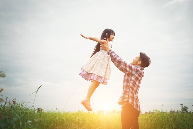 Daddy carrying his daughter with nature and sunlight, enjoyment