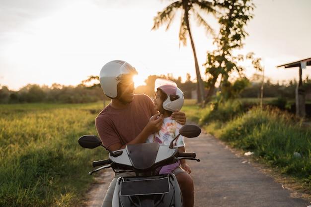 パパは彼女の娘がヘルメットを固定するのを助けます
