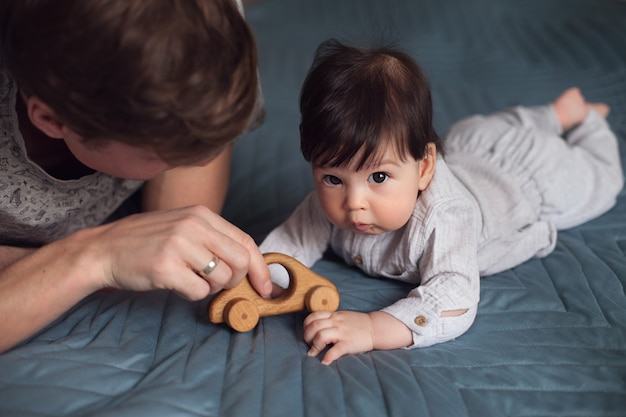 Daddy and his little son lie on the bed and play with a toy wooden car