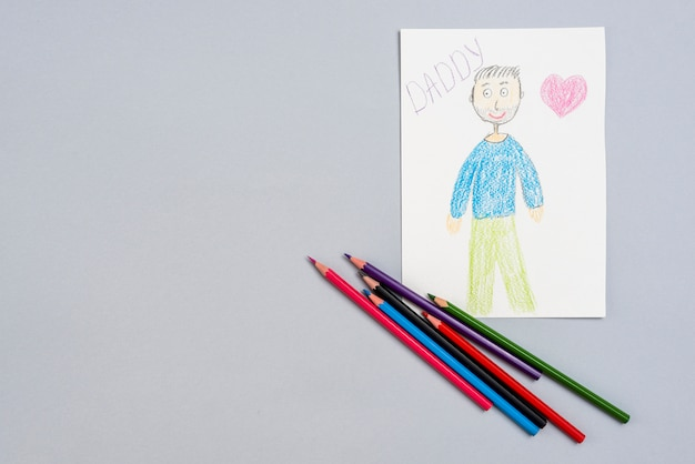 Daddy inscription with man drawing and pencils