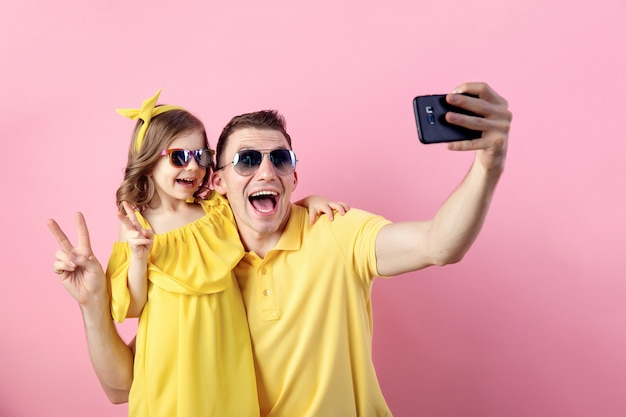 Daddy and little daughter doing selfie with smartphone