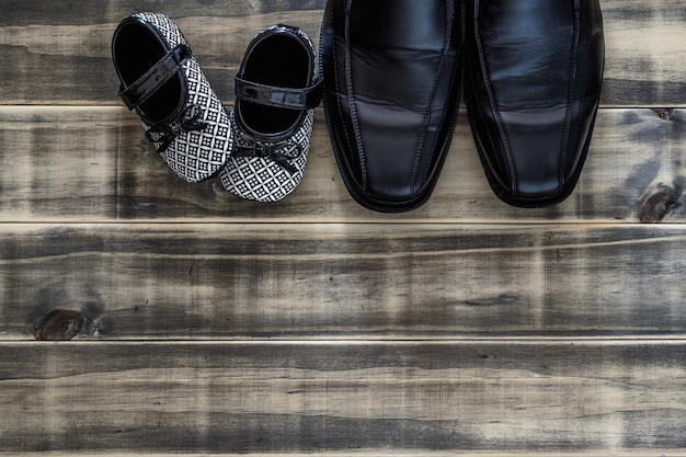 Daddy's black business shoes and black and white kids sneakers side by side on grunge rusty wood, concept of family, single parent and father's day, top view flat lay with copy space.