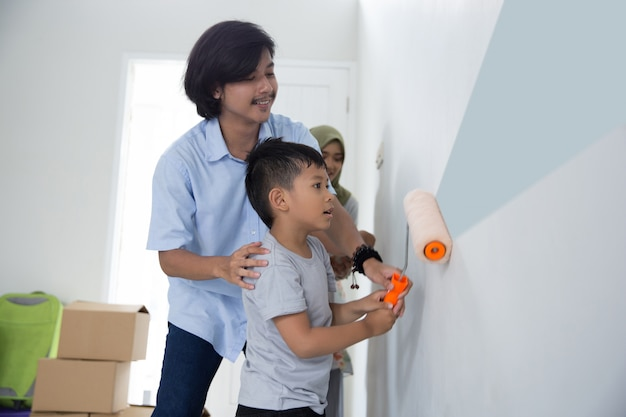 Daddy and son paint their new house