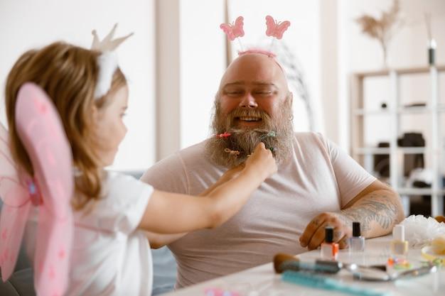 Папа с повязкой на голове играет с маленькой дочкой в костюме феи за столом в светлой комнате