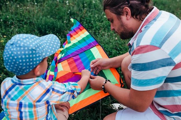 飛んでいる凧を集める小さな就学前の男の子とパパ