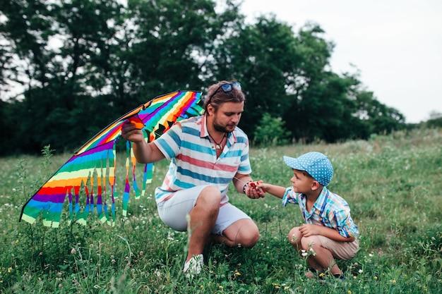 幼稚園の男の子とパパは空飛ぶ凧を飛ば