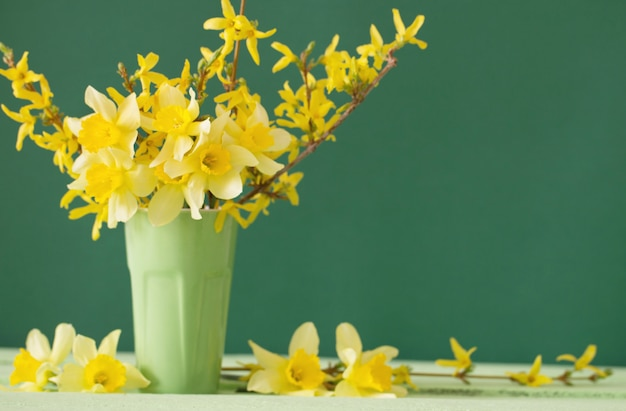 Daffodil in vase on green space