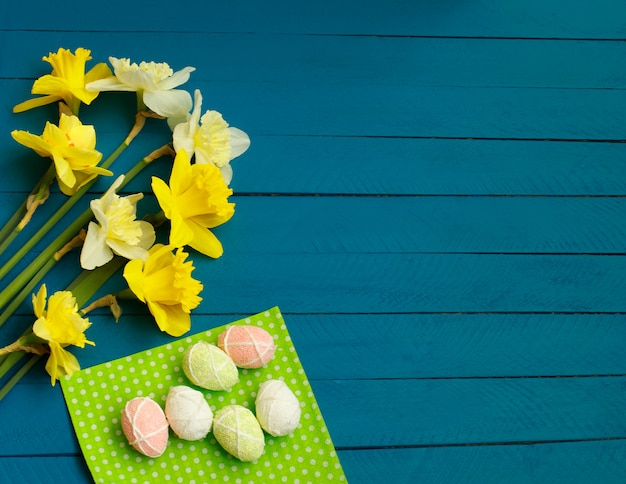 Daffodils and eggs on blue wooden