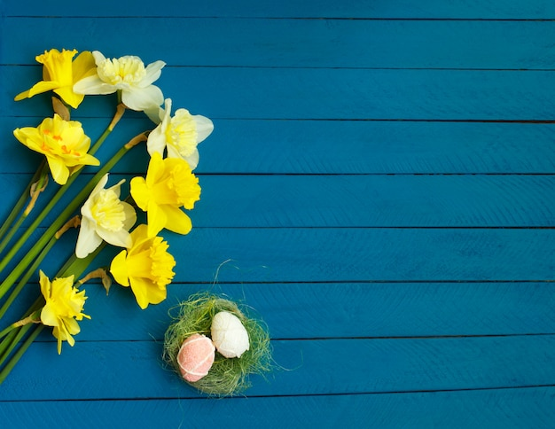 Daffodils and eggs on wooden